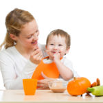 młoda mama karmi syna jedzeniem zwiększającym odporność